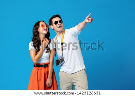 Portrait of a young happy smiling interracial tourist couple in casual attire enjoying their summer vacation getaway together in blue studio background #1423126631