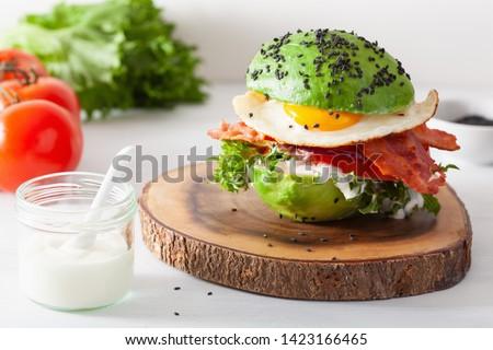 keto paleo diet avocado breakfast burger with bacon, egg, tomato Royalty-Free Stock Photo #1423166465