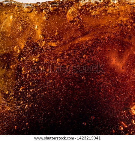 Close up view of the ice cubes in dark cola background. Texture of cooling sweet summer's drink with foam and macro bubbles on the glass wall. Fizzing or floating up to top of surface. #1423215041