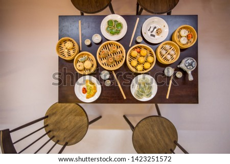 Close-up background Of dining table simulation to look appetizing (dim sum, cups, tea cups, chopsticks) with chairs for ready to sit for customers #1423251572