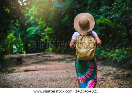 Young girl with backpack enjoying  travel nature in the forest Lush green trees. The back view of the girl who is walking travel in the forest. In the summer, Travel relax, Travel Thailand. #1423454825