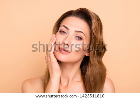 Close up photo beautiful amazing mature she her lady overjoyed after salon spa procedures aesthetic pretty ideal appearance nude arm hand palm touch cheek perfection isolated pastel beige background #1423511810