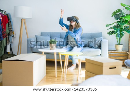 Young blonde woman wearing virtual reality glasses playing a simulation game sitting on the sofa around cardboard boxes moving to a new house #1423573385