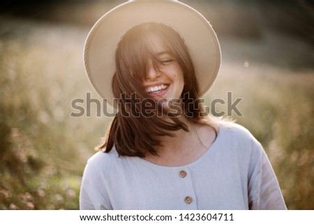 Stylish girl in rustic dress smiling and waving hair in sunny meadow in mountains. Portrait of happy boho woman in countryside at sunset, positive vibes, rural simple life. Atmospheric image #1423604711