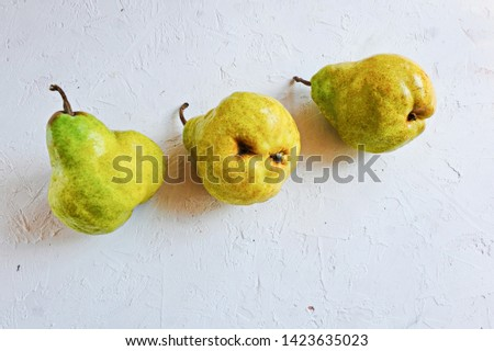 Trendy ugly organic fruits - three yellow pears on the table with copy space for text. Vertical orientation. Buying imperfect products is a way to deal with food waste. Horizontal. #1423635023