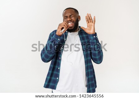 Handsome Afro American man in casual clothes is listening to music using a smart phone and smiling. #1423645556