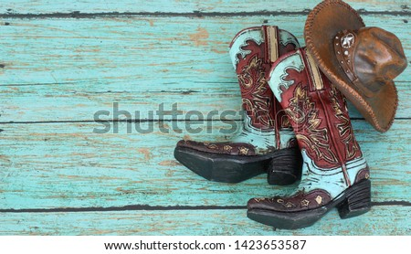 teal and burnt red cowboy boots and hat on a teal wooden background with writing space  #1423653587