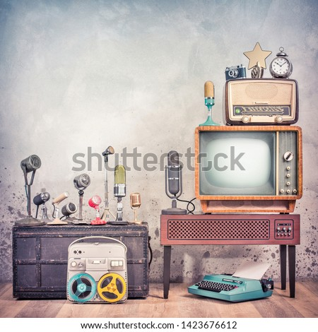 Retro studio microphones set, outdated TV, old broadcast radio, journalist's reel to reel tape recorder, aged clock, film camera, golden award star, typewriter. Journalism concept. Vintage style photo #1423676612