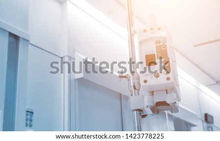 Medical drip and infusion pump for saline or salt fluid water. For patient treatment in clinic or hospital with needle injection into blood stream. Cool soft blue color tone background