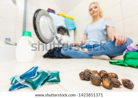 Woman in bathroom comparing washing soap nuts and detergent gel pods. Alternative household objects, toxin free and chemical laundry. #1423851371