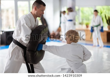 Improving strength. Curly blonde-haired boy loving martial arts improving his strength Royalty-Free Stock Photo #1423910309