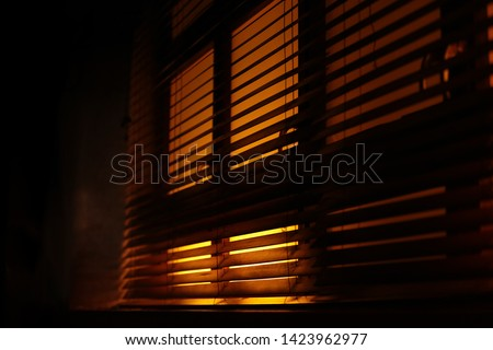 Dark, moody atmosphere set by yellow light softly piercing through the blinds. The shutters create a lovely contrast between light and shadow.Also a concept of mafia, fear, kidnapping, sleep, sunlight #1423962977