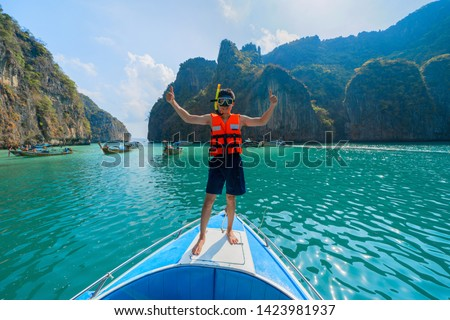 An Asian man, a tourist, standing on a boat to snorkeling in Krabi with turquoise blue sea, Andaman Sea in Thailand. #1423981937
