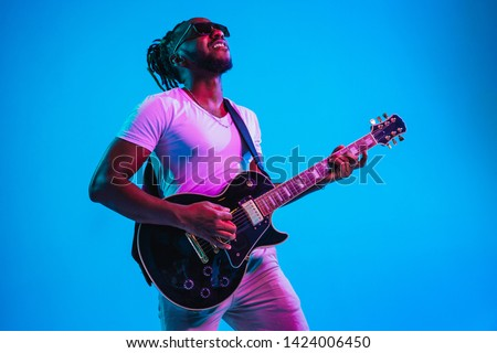 Young african-american musician playing the guitar like a rockstar on blue studio background in neon light. Concept of music, hobby. Joyful attractive guy improvising. Retro colorful portrait. #1424006450
