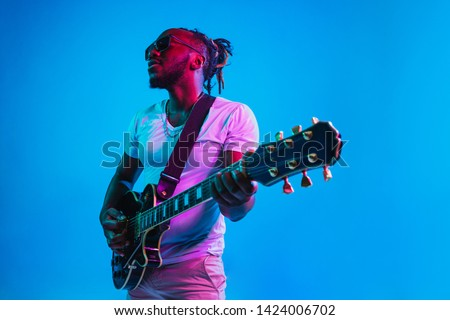 Young african-american musician playing the guitar like a rockstar on blue studio background in neon light. Concept of music, hobby. Joyful attractive guy improvising. Retro colorful portrait. #1424006702