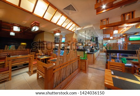 """MOSCOW - SEPTEMBER 2014: The interior of the popular Japanese chain of restaurants """"YAKITORIYA"""" in Moscow. Open kitchen bar counter in the middle of the hall #1424036150"""