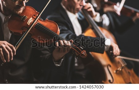 Professional symphonic string orchestra performing on stage and playing a classical music concert, violinist in the foreground #1424057030
