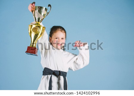 sport success in single combat. practicing Kung Fu. happy childhood. winner little girl in gi sportswear. small girl with champion cup. martial arts. energy and activity for kids. Striking the pose. #1424102996