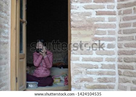 Caravanserai, Kashan, Iran - October 2017 : An asian tourist applying make up in the morning inside a caravanserai near Kashan in Iran. #1424104535