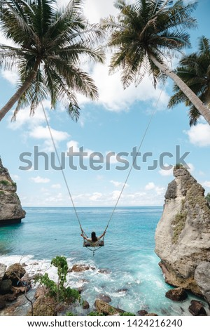 Young girl swinging on a swing overlooking the blue sea. Travel adventure on paradise tropical island. A young girl swinging on a swing between palm trees on the beach of a tropical island #1424216240