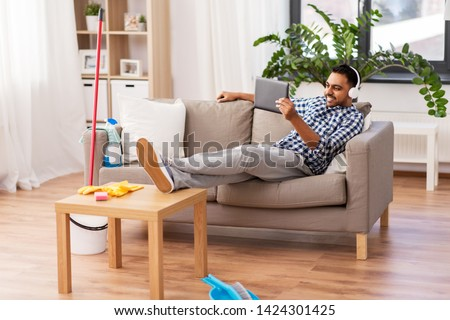people, housework and housekeeping concept - indian man in headphones listening to music on tablet computer after home cleaning #1424301425