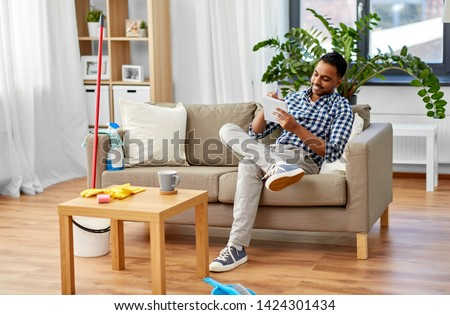 household and time management concept - smiling indian man making to do list in notebook after home cleaning #1424301434