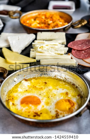 Colorful,fresh,organic,traditional village Turkish Breakfast at the wooden table on fabric table cloth.Used copper egg pan,ceramic casserole and bamboo bowls.Close up taken,top view #1424559410