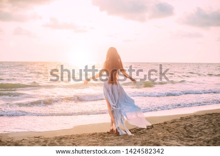 mysterious mermaid with long black hair slowly walks in water of ocean, sea nymph listens to wind like wave in long blue dress with flying train, looks at divine sunset. photo from the back, no face #1424582342