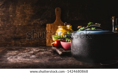 Cast iron pot with fresh herbs, spices and kitchen utensils for tasty cooking on rustic table. Healthy eating. Homemade cooking. Dark. Still life. Food background. Copy space #1424680868