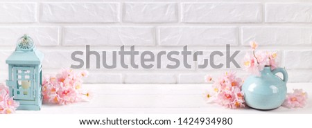 Floral still life banner layout. Pink cherry blossoms, blue vase, candle in candleholder on wooden background near dy brick wall. Selective focus. Place for text. #1424934980