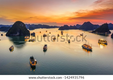 Aerial view of sunset and dawn near rock island, Halong Bay, Vietnam, Southeast Asia. UNESCO World Heritage Site. Junk boat cruise to Ha Long Bay. Popular landmark, famous destination of Vietnam Royalty-Free Stock Photo #1424935796