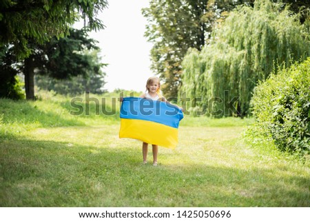 Child carries fluttering blue and yellow flag of Ukraine in field. Ukraine's Independence Day. Flag Day. Constitution day. Girl in traditional embroidery with flag of Ukraine #1425050696