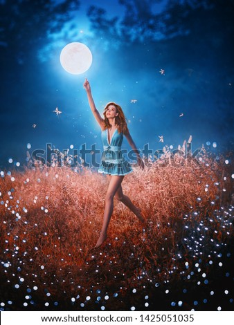 pretty leggy beauty with flying flowing hair runs through field of fallen stars behind mystical floating moon. Amazing art photo with creative colors. girl in image of night fairy in short blue dress