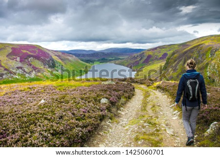 Tourist walking down from Cairn Lick to Loch Lee. Angus, Scotland, UK. Cairngorms National Park. #1425060701