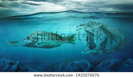 Fish swims among plastic bag ocean pollution. Environment concept #1425076076