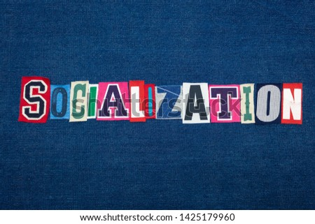 SOCIALIZATION collage of word text, multi colored fabric on blue denim, socially adept and confidence concept, horizontal aspect