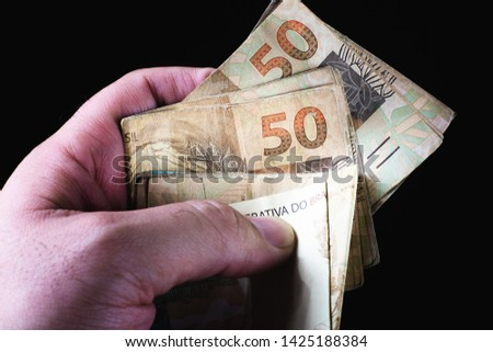 Brazilian currency. Money from Brasil. Dinheiro, Real, Reais, Brazilian Real. Picture of man holding many 50 real notes with black background.