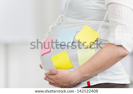 Side view of pregnant woman in office with post-it notes stuck on belly in office #142522408