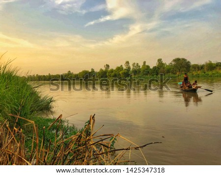 Shinnng river water of 5 river called Punjab. It's evening time d beautiful pic of boat doing fishing can be seen.