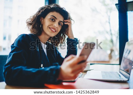 Portrait of stylish beautiful hipster girl smiling at camera while holding smartphone in hand and working remotely at laptop device using wireless internet.Positive young woman studying at computer #1425362849