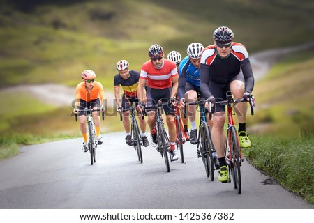 Cyclists out racing along country lanes in the mountains in the United Kingdom. #1425367382