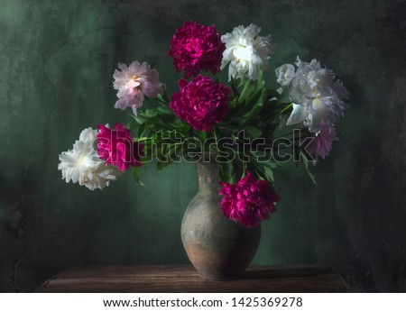 Classic still life with beautiful white and purple peony flowers bouquet in ancient jug. Art photography. #1425369278