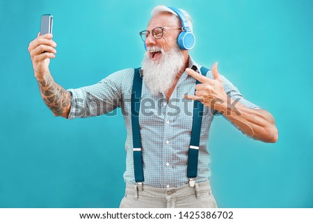 Senior hipster man using smartphone app for creating playlist with rock music - Trendy tattoo guy having fun with mobile phone technology - Tech and joyful elderly lifestyle concept - Focus on face #1425386702