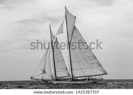 Vintage yachts race in Barcelona. Old ships and boats in the sea. Black and white photos of nautical sports in the ocean. Regatta in mediterranean sea. Sails, mast, sheet, canvas in the sky. Holidays #1425387707