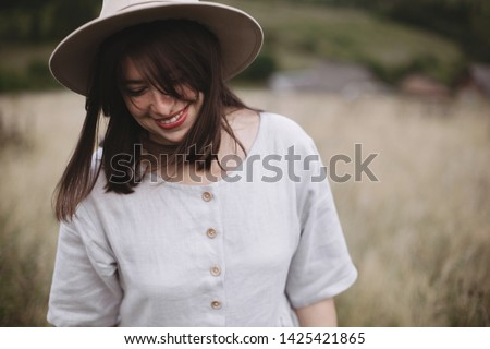 Stylish girl in linen dress and hat walking among herbs and wildflowers in field. Boho woman smiling and relaxing in countryside, simple slow life style. Space for text. Atmospheric image Royalty-Free Stock Photo #1425421865