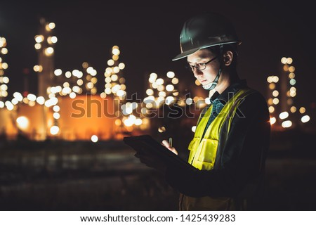 Asian man engineer using digital tablet working late night shift at petroleum oil refinery in industrial estate. Chemical engineering, fuel and power generation, petrochemical factory industry concept #1425439283