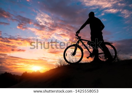 Silhouette of sports person cycling on the meadow on the beautiful sunset. Young man riding bicycle. #1425558053