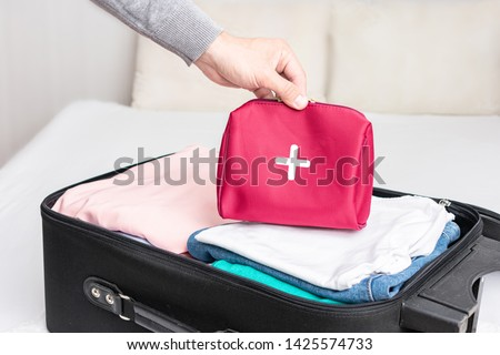 A man collect the suitcase on the trip, clothes for the road and first aid kit for extraordinary event, men's hand, top view, cropped image, toned #1425574733