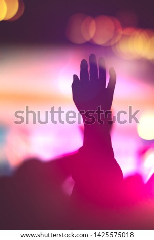 Silhouette photo of Christian worship God together in Church hall in front of music stage Night of worship.Raised hand and praise worship the LORD.Christian concert background.  #1425575018