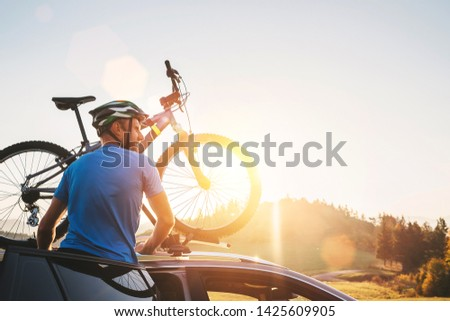 Man taking his bicycle from car roof. Mountain biking concept Royalty-Free Stock Photo #1425609905